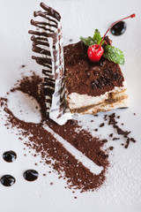 Tiramisu on white plate with decoration from chocolate, cherry and mint. Sweet dessert serving in restaurant, close up picture