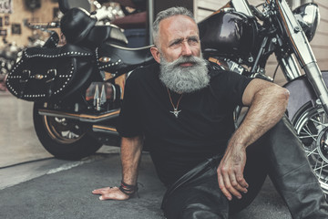 Dreamy old man locating near motorcycle