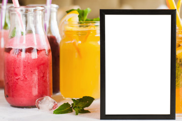 Blank picture frame with fresh fruit drinks behind. Food blogs, menu and recipes for web sites of cafe and restaurant, close up picture with copy space
