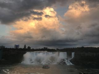 A tour boat passes the American Falls and the Bridal Veil Falls of the Niagara Falls at dusk