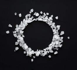 crystals of sea salt are scattered in the form of a round frame