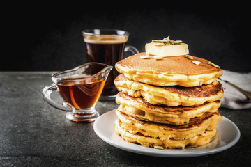 Autumnal traditional food. Stack of pumpkin pancakes with butter, pumpkin seeds and maple syrup. With a cup of coffee. On a black stone table. Copy space