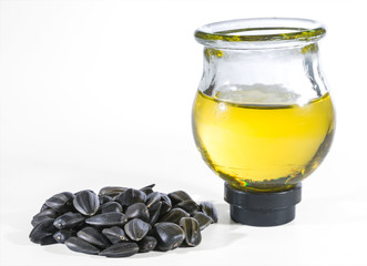 Sunflower seeds and sunflower oil in a round glass jar isolated on a white background.
