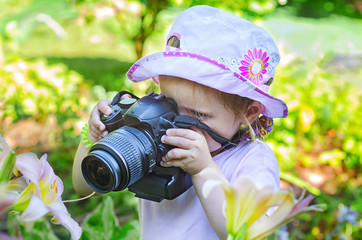 Little girl photographer takes pictures of flowers