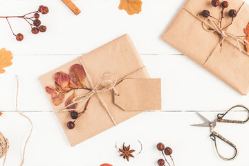 Autumn composition. Gift, autumn leaves, cinnamon sticks, anise star on wooden white background. Flat lay, top view, close up