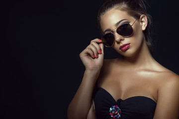 Close up portrait of young gorgeous tanned model with casual updo hair and beautiful make up wearing trendy aviator sunglasses. Isolated on black background. Copy-space. Studio shot
