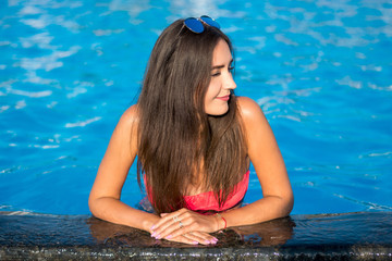Beautiful young brunette woman with long hair in pink bikini keeps his hands on the edge a pool