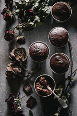 Molten chocolate cakes in cups. Dried roses and artichokes for decoration. Overhead view
