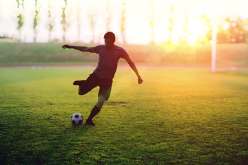 Soccer player is shooting a ball in stadium at sunset.