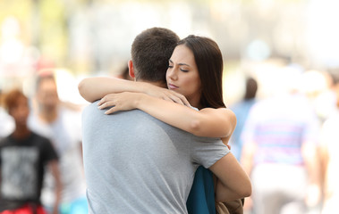 Couple with problems hugging on the street
