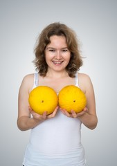 Young beautiful woman holds melons in hands above her breast. Plastic surgery and silicone implants concept.