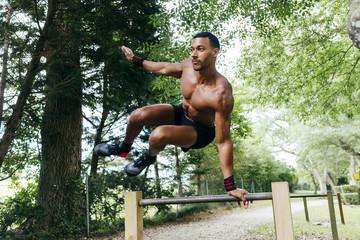 Black muscular man exercising in park
