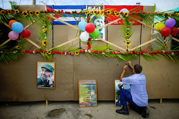 A man hangs pictures of late Cuban president Fidel Castro on a stage to be used during celebrations of what would have been his 91st birthday in San Antonio de los Banos