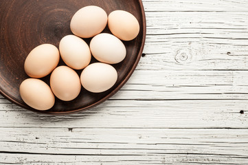 chicken eggs in clay plate on white wooden background