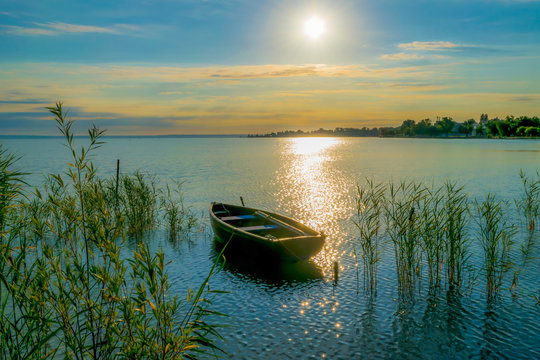 Rowing boat on lake at sunset.  Small wooden rowing boat on a calm lake at sunset.