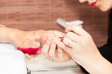 Laying nail polish on a woman's hands