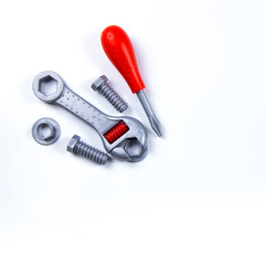 Kids construction toys tools: colorful screwdrivers, screws and nuts on wooden background. Top view. Flat lay. Copy space for text