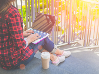 Young pretty woman sitting with laptop having coffee on the stairs for outsite working. Online business concept and front view with copy space.