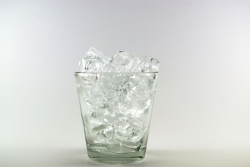 Ice cube in the glass over the white background, soft focus