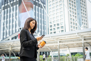 Business woman using phone with coffee in hand walking on the street with office buildings in the background
