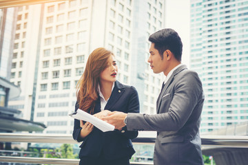Business man pointing at document with smile and discussing something with her coworker while standing in front of office.