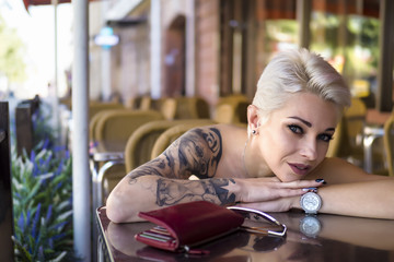 Tattoed woman in cafe