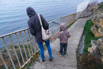 A woman with a child went down the stairs to the sea