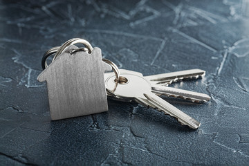estate concept, keychain with house symbol, key on wooden background