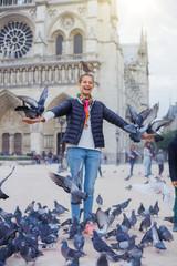 Girl with birds near Notre Dame de Paris cathedral in Paris, France