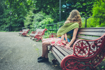 Mother with baby in sling resting on park bench