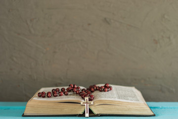 Bible and the crucifix on a blue wooden table. Beautiful background.Religion concept.