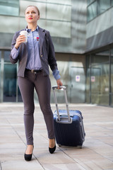 Smiling woman with baggage and coffee