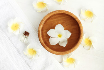 Tropical spa. Frangipani (Plumeria) flower floating in bowl of aroma water with essential oils, white towel background, top view.