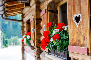 Typical bavarian or austrian wooden window with red geranium flowers on house in Austria or Germany Fototapete