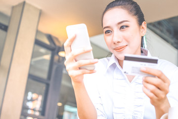 A woman's hand holds a credit card and uses uses a mobile phone to shop online.