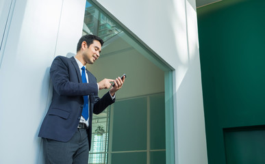 Businessman using mobile phone indise office building,after work lifestyle