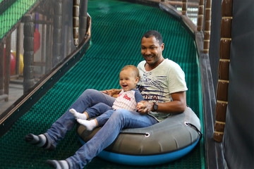 Father and son sliding at a indoor playgrounds