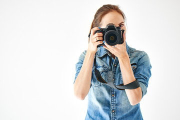 Portrait of a girl photographer on a white background