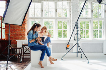 Girl photographer shows the picture of the model