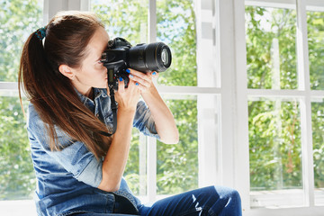 Portrait of female photographer with camera in hand