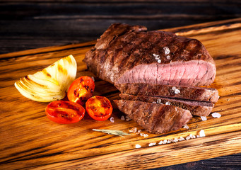 Wall Mural - Medium rare grilled Steak Ribeye with fried onions and cherry tomatoes on a wooden board