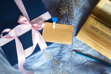 Dark blue gift box with  ribbon decoration with book and flower on polka blue paper , Happy Father's Day or celebration gift concept , top view and overhead shot , right copy space background