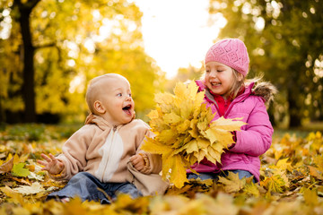 Baby boy having fun in the autumn park with her sister