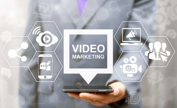 Video Marketing Online Business Mobile concept. Man offers smart phone with video marketing speech bubble icon on a virtual graphical user interface.