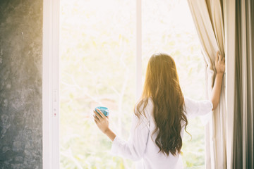 Asian women drinking coffee and waking up in her bed fully rested and open the curtains in the morning to get fresh air on sunshine
