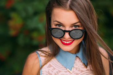 Beautiful girl lowering her sunglasses and looking happy at came
