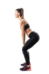Side view of strong fitness gym girl swinging kettlebell in lower position. Full body length portrait isolated on white studio background