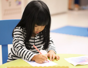 Asian children cute or kid girl learning for coloring or hand drawing paint on white paper and colorful table with chair at nursery or pre school on soft focus