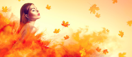 Beautiful fashion woman in autumn yellow dress with falling leaves posing in studio