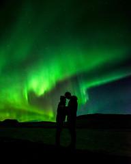 Silhouette eines Paares vor Nordlichtern